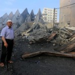 Fire is seen as a Palestinian man walks amidst the remains of a tower building housing offices, which witnesses said was destroyed by an Israeli air strike, in Gaza City August 26, 2014. Israeli air strikes launched before dawn on Tuesday killed two Palestinians and destroyed much of one of Gaza's tallest apartment and office buildings, setting off huge explosions and wounding 20 people, Palestinian health officials said. Israel had no immediate comment on the attacks that took place as Egyptian mediators stepped up efforts to achieve an elusive ceasefire to end seven weeks of fighting. Israel launched an offensive on July 8, with the declared aim of ending rocket fire into its territory. Photo by Mohammed Asad